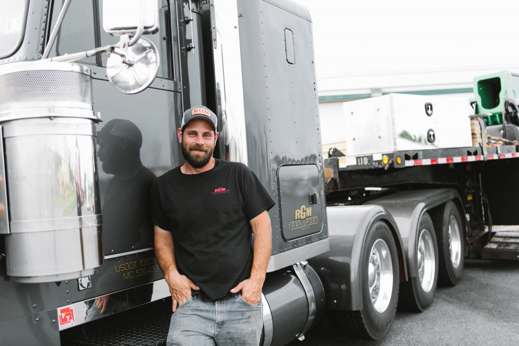 New Venture Truck Driver Standing In Front of Big Rig